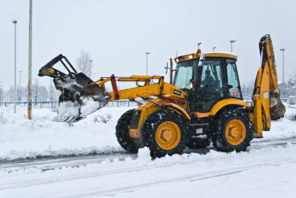 yellow snow plow cleaning a road